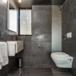 Alchemy lightHouse L ADU bathroom with wall-mounted toilet and floor to ceiling tile.